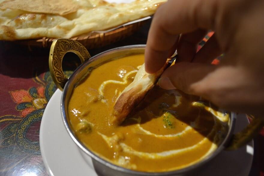 タージマハル志免店の野菜カレーにナンを浸す